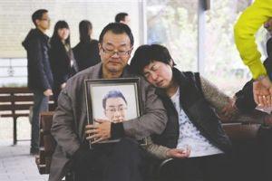 魏则西的父母怀抱他的遗像