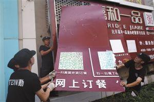 8月8日,北京朝阳区北京像素北区,执法人员正在拆除一家无照经营饭店的户外广告。